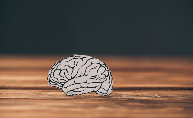paper with brain as dementia symbol on black background