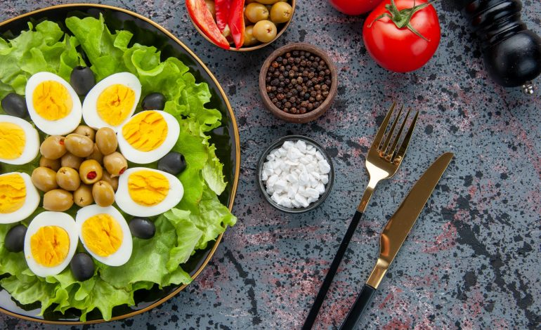 top view delicious egg salad with seasonings and olives on light background health tea bread