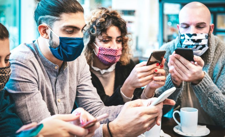 Worried people with face mask checking news on mobile smart phones